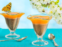 Two glasses with dessert and the butterfly, close-up. Two glasses with orange-chocolate jelly and a butterfly close-up on a background of blue sky and blooming royalty free stock image