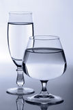 Two glasses. With a drink, beautifully refracting monophonic light Stock Photography