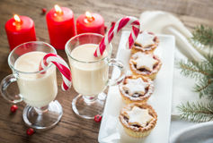 Two glasses of eggnog with mince pies Royalty Free Stock Photos