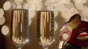 Two glasses filled with bubbly champagne and carnival masquerade mask. Bokeh lights on the background. Two glasses filled with bubbly champagne and red carnival stock video