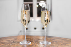Two glasses filled with champagne on a antique table Royalty Free Stock Image
