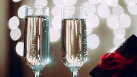 Two glasses filled with champagne and bokeh lights on the background. Two glasses filled with champagne and gift with red ribbon. Bokeh lights on the background stock video