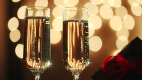 Two glasses filled with champagne and bokeh lights on the background. Two glasses filled with champagne and gift with red ribbon. Bokeh lights on the background stock footage
