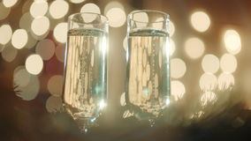 Two glasses filled with champagne and bokeh lights. Two glasses filled with champagne and gift with red ribbon. Bokeh lights on the background. Fir tree branch stock footage