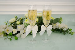 Two glasses filled with champagne, with flowers. Two glasses filled with champagne with flowers Royalty Free Stock Photography