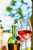 Two glasses filled with red wine and bottle in background. Two wine glasses filled with red wine and wine bottle in background. Soft focus Stock Photography