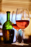 Two glasses filled with red wine and bottle in background. Two wine glasses filled with red wine and wine bottle in background. Soft focus Royalty Free Stock Images