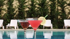Summer drink near the pool. Two glasses filled with a summer drink in the summer heat near the pool stock video footage