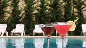 Two Glasses Filled With A Summer Drink In The Summer Heat Near The Pool.  stock video footage