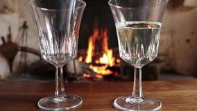 Two glasses filled with white wine on the background of a burning fireplace. White wine is poured into two glasses against the background of a burning fireplace stock video
