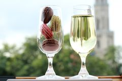Two glasses of French macarons and white wine Stock Photos