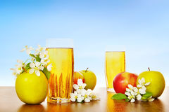 Two glasses of fresh apple juice with ripe apples against blue Royalty Free Stock Photography
