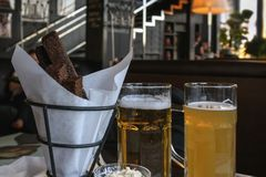 Two glasses of fresh beer different varieties and salty snack, real scene in pub, bar. Oktoberfest, beer festival stock images