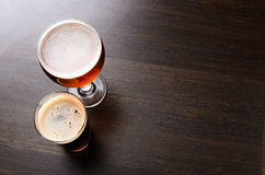 Two glasses of fresh beer on pub counter. Two glasses of fresh beer on pub table, view from above Stock Photos