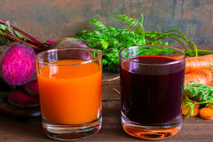Two glasses of fresh carrot and beetroot juice. healthy drink. Two glasses of fresh carrot and beetroot juice with sliced vegetables on wooden background Royalty Free Stock Image