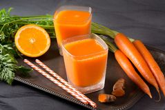 Two Glasses of Fresh Carrot-Orange Juice. With turmeric root and drinking straws on a rustic serving tray stock photography