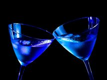 Two glasses of  fresh cocktail with ice make cheers. On blue tint light with space for text Stock Photo