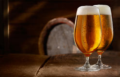 Two glasses of fresh foamy beer. On a table in a vintage beer cellar with a barrel in the background Royalty Free Stock Images