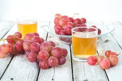 Two glasses of fresh grape juice. And red grapes on a white wooden rustic table royalty free stock photos