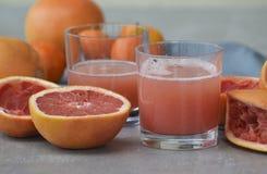 Two glasses of fresh grapefruit juice on gray background. royalty free stock image