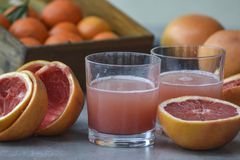 Two glasses of fresh grapefruit juice on gray background. stock photography