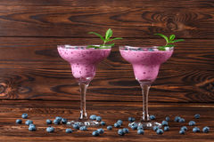 Two glasses with a fresh smoothie. Tasty smoothies on a wooden background. Natural drinks with blueberries, mint and raspberries. Two glasses of fresh and cold Stock Images
