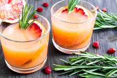 Two glasses of fresh summer drink with blood orange and rosemary on a dark wooden background. Selective focus stock photos