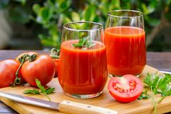 Two glasses of fresh tomato juice and tomatoes on a wooden cutti Stock Photos