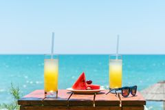 Two glasses of fresh tropical fruit juice on the beach, and a plate with grapes and watermelon on the table, against the sea. Holi stock images