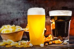 Two glasses with freshly poured light unfiltered and dark beer n Stock Image