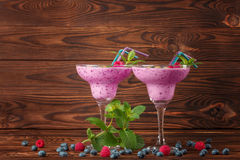 Two glasses full of fresh smoothies on a wooden background. Organic and natural beverages with berries, milk, and mint. Two margarita glasses of cold and fresh Stock Photo