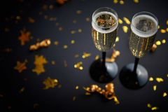 Two glasses full of sparkling champagne wine with golden decoration. Of confetti and serpentines on black elegant background. Top view with copy space. Festive stock photo