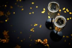 Two glasses full of sparkling champagne wine with golden decoration. Of confetti and serpentines on black elegant background. Top view with copy space. Festive stock photos