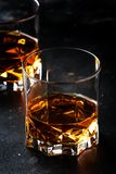 Two glasses of golden scotch whiskey on dark old bar table background, selective focus royalty free stock images