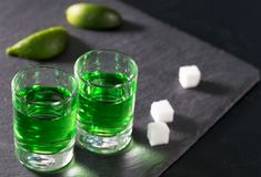 Two glasses with green absinthe lime and sugar. On a dark background stock image