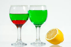 The two glasses of green and red liquor. The two glasses of transparent green and red liquor and lemon Stock Image