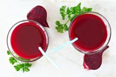 Two glasses of healthy beet juice, downward view over marble. Two glasses of healthy beet juice, downward view over a white marble background stock photo
