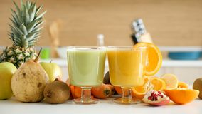 Two glasses with healthy and organic juices. In the kitchen next to the fruits and vegetables it was made of. Detox and health stock footage