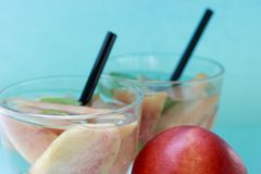 Two glasses with homemade iced tea with pieces of peaches. Summer refreshing drink royalty free stock images