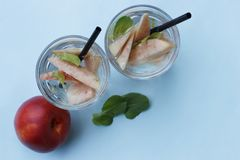 Two glasses with homemade iced tea with pieces of peaches. Summer refreshing drink, top view stock photo