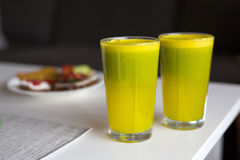 Two glasses of homemade juice. Homemade Juice Made of orange, apple, spinach, lime and ginger Stock Images