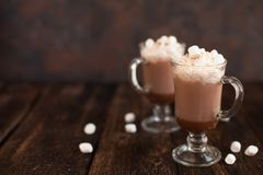 Two glasses with Hot chocolate garnished with whipped cream, mar