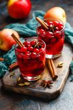 Glasses with hot punch for winter. Mulled wine. Two glasses with a hot drink of cranberries and apples with spices, mulled wine, punch or grog Royalty Free Stock Image