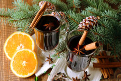 Two glasses of hot mulled wine with,orange and spices on a background of traditional Christmas decorations. Stock Photo