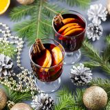Two glasses of hot mulled wine with spices and sliced orange. Christmas drink with candle and decorations. Top view stock image