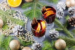 Two glasses of hot mulled wine with spices and sliced orange. Christmas drink with candle and decorations. Top view stock photography