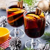 Two glasses of hot mulled wine with spices and sliced orange. Christmas drink with decorations. Top view royalty free stock images