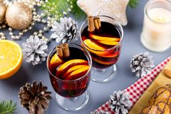 Two glasses of hot mulled wine with spices and sliced orange. Christmas drink with decorations. Top view royalty free stock image