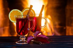 Two glasses of hot mulled wine with spices on wooden table against fireplace. stock photos