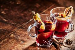 Two glasses of hot spicy Gluhwein for Christmas. Two glasses of hot spicy Gluhwein to celebrate Christmas with stick cinnamon and star anise on a rustic wooden Royalty Free Stock Images